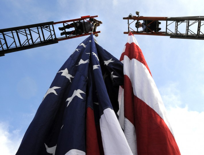 Baltimore City Firefighters take down the large American Flag used at the ceremony. Mayor Stephanie Rawlings-Blake led a march of dignitaries, veterans, and military personnel down Charles Street from the Washington Monument (Charles & Centre Streets) to the ceremonial stage at the War Memorial Plaza. (Lloyd Fox/Baltimore Sun)
