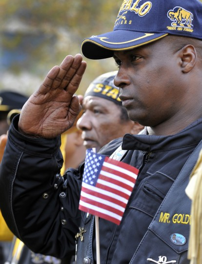 Cedric Harris (R) and Harry Ford (L) both veterans salute during the National Anthem. Mayor Stephanie Rawlings-Blake led a march of dignitaries, veterans, and military personnel down Charles Street from the Washington Monument (Charles & Centre Streets) to the ceremonial stage at the War Memorial Plaza. (Lloyd Fox/Baltimore Sun)