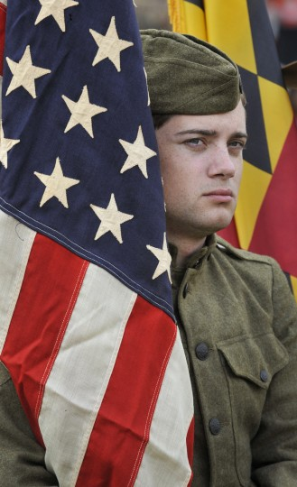 Tyler Mink a park ranger at Fort McHenry wrapped in a 48 star WW1 flag. Mayor Stephanie Rawlings-Blake led a march of dignitaries, veterans, and military personnel down Charles Street from the Washington Monument (Charles & Centre Streets) to the ceremonial stage at the War Memorial Plaza. (Lloyd Fox/Baltimore Sun)