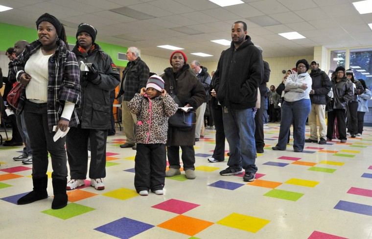BALTIMORE, MD: Tyler Spencer, 5, third from left, got a civics lesson this morning as she waited in line with her grandmother, Terri Clay, second from left, who was voting at Guilford Elementary School. Voters in four lines filled the cafeteria before 9 a.m. on Election Day. (Amy Davis/Baltimore Sun)