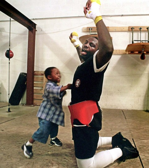 "Hasim Rahman, a Baltimore native, takes a punch from his 4-year-old son Sharif. ""The Rock,"" a 20-to-1 underdog, knocked out champion Lennox Louis in 2001 to win the heavyweight title. (Jed Kirschbaum/Baltimore Sun)"
