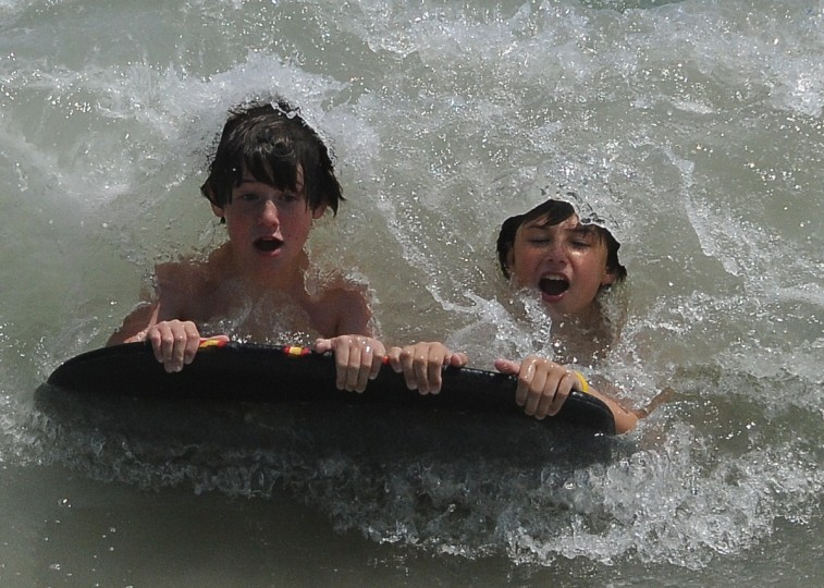 "Frank Tewey is this week's ""Life's a Beach"" winner for the photo of his sons Adam and Noah sharing a boogie board in Ocean City. Tewey used a Nikon D300 zoomed to 200mm to catch the wave just before it crashed over them. Here is a critique from Baltimore Sun photo editor Jerry Jackson: ""Having a good camera with a fast motor drive can all the difference when trying to capture an image like this. A high shutter speed helps catch Noah's face perfectly framed by the water that would engulf him a millisecond later."""