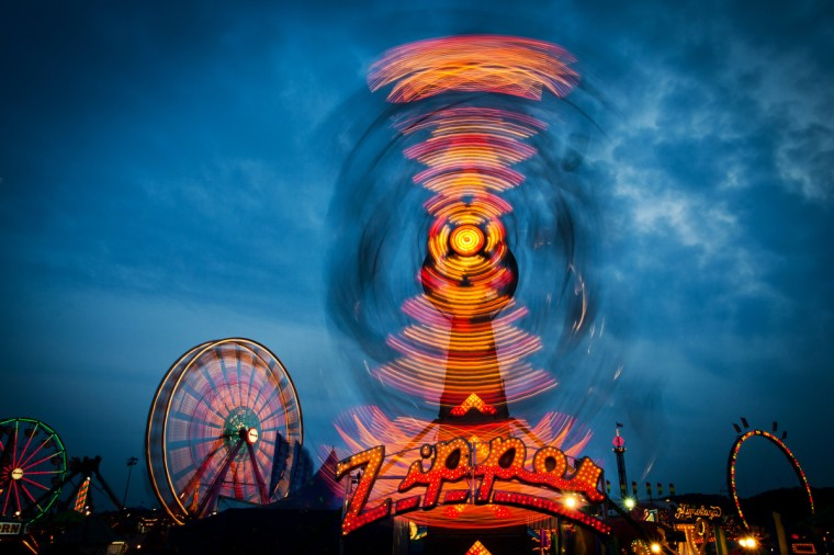 "The winner of this week's Baltimore Sun Reader SunShots series ""At the fair"" is Joe Messenger for his photo of the Zipper ride at the Maryland State Fair last year. The image was taken with a Canon 5D Mark II with the aperture at f22 for 1 Second at ISO 100. ""This photo was taken as the sun was going down and all of the beautiful lights were coming on to light up the fair grounds. As a child this was one of my favorite ride to be on and I had shot a photo of this during the day but I just knew by coming back at night this photo would just be outstanding."" Here is a critique by The Baltimore Sun's photo editor Jerry Jackson: ""Joe's decision to make this photo at twilight really gives the image an extra dimension. The dark blue sky helps the reds and orange lights pop. The exposure was just long enough to capture the motion without washing out the color."""