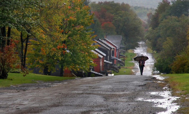 "The winner of this week's Reader SunShots series ""The Open Road"" is Kevin Moore for his picture from the Eckley Miners Village in Pennsylvania. He took the picture with a Canon 40d DSLR camera. Here is a critique from director of photography Robert Hamilton. ""I like the mood of this photograph. The dreary weather works well with the fall colors. The photographer also did a great job of composing the image, placing the subject in an ideal spot that separates the woman with the umbrella from the background."""