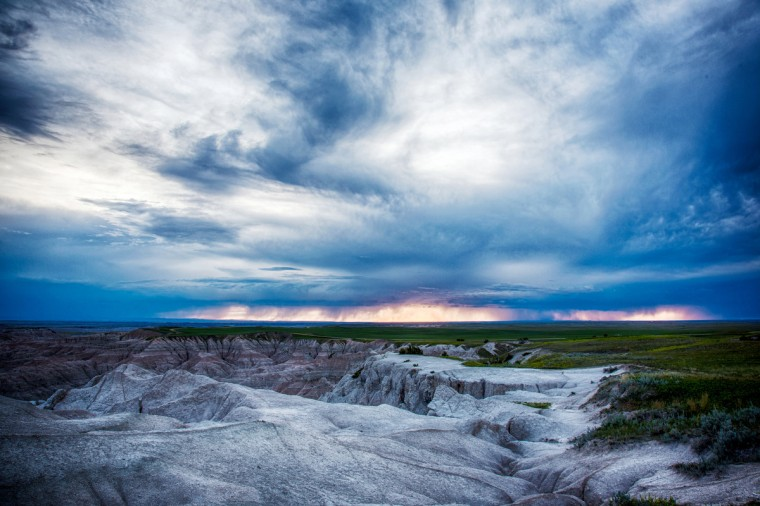 "The winner of this week's SunShots series ""Stormy"" is John Jake Jakubik for his picture taken in the Badlands National Park in South Dakota. The picture was taken with a Canon 5D III. Here is a critique by director of photography Robert Hamilton. ""This a beautiful picture. The photographer used a technique know as High Dynamic Range (HDR) to produce the image. Basically you compile a series of images made with varying exposures to produce a singular picture. This way you still get the dramatic clouds while still producing detail through the midtones and shadows of the photograph. Sometimes this effect can be overdone to the point where the picture looks almost cartoonish in nature. In this case the photographer used the technique effectively and with the proper restraint."""