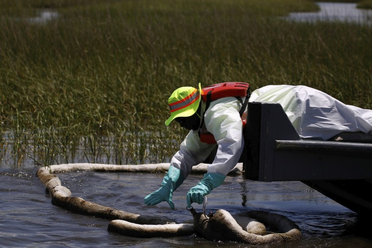 June 24, 2010 - A worker pulls up a boom soaked in oil in the wetlands in Cocodrie, La. (Photo by Chris Graythen/Getty Images)