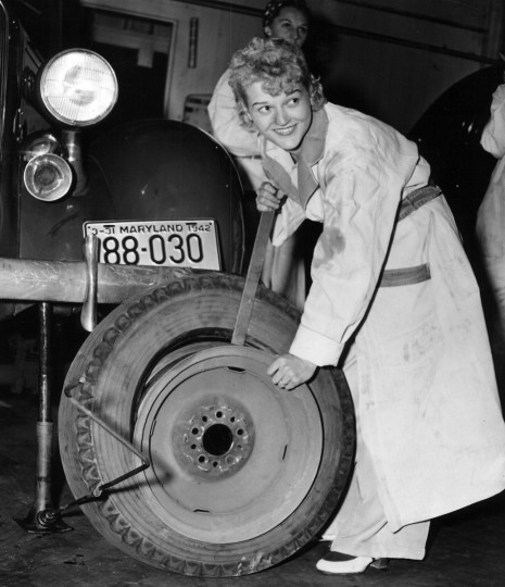 Irene Grzech of the Red Cross Motor Corps changes a flat. Nearly all the aid volunteers were women, and many took mechanics courses to enable them to make needed repairs. (Baltimore Sun)