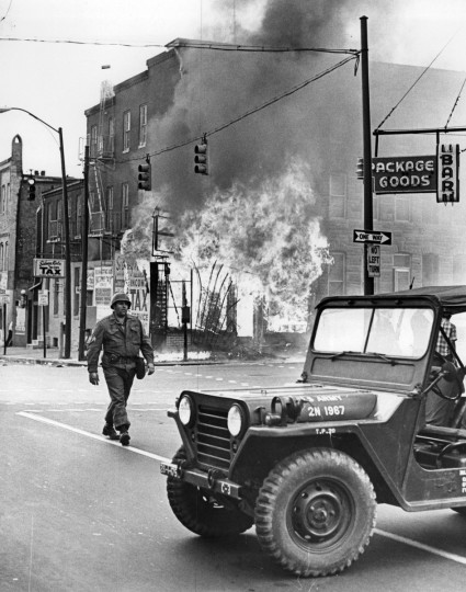 A National Guardsman can do little as a shop burns out of control amid the 1968 riots. Insurers estimated damage in Baltimore at $8 million to $10 million during the unrest. (William H. Mortimer/Baltimore Sun)