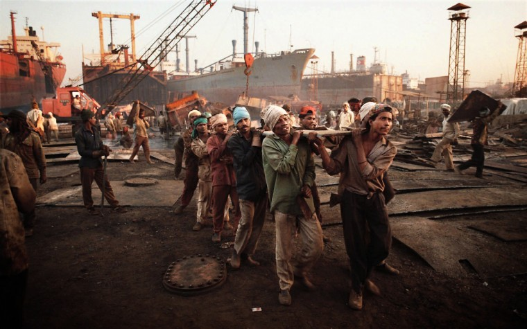 Workers carry heavy sheets of steel as they break up obsolete U.S. warships on the shores of Alang, India, in 1997, at considerable risk to laborers and the environment. (Perry Thorsvik /Baltimore Sun)