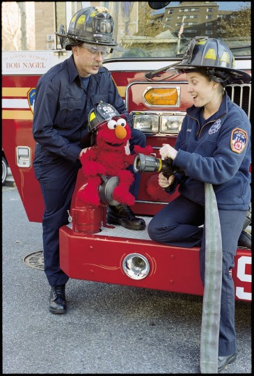 In one of four Sesame Street episodes airing in response to September 11th, New York City firefighters comforted a frightened Elmo after he witnessed a fire in Hooper's Store. The firefighters invite Elmo to their fire station, where he learns more about what they do. (Richard Termine/Sesame Workshop/Handout photo)