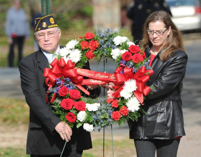 Post 47 Commander Richard Ferguson and Unit 47 President Candice Bossoli carry a wreath to the memorial during the Veterans Day ceremony held in Tydings Park Monday morning. (Nicole Munchel/Aegis)