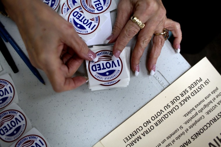 "A poll worker stacks ""I Voted"" stickers before handing them to voters at Jan Kaminis Platt Regional Library in South Tampa, Florida. With 29 electoral votes, Florida was key to the strategies of both U.S. President Barack Obama and Republican challenger Mitt Romney. By Wednesday morning, the winner of the state's presidential vote was still uncertain. (Carolina Hidalgo/Tampa Bay Times/MCT Photo)"