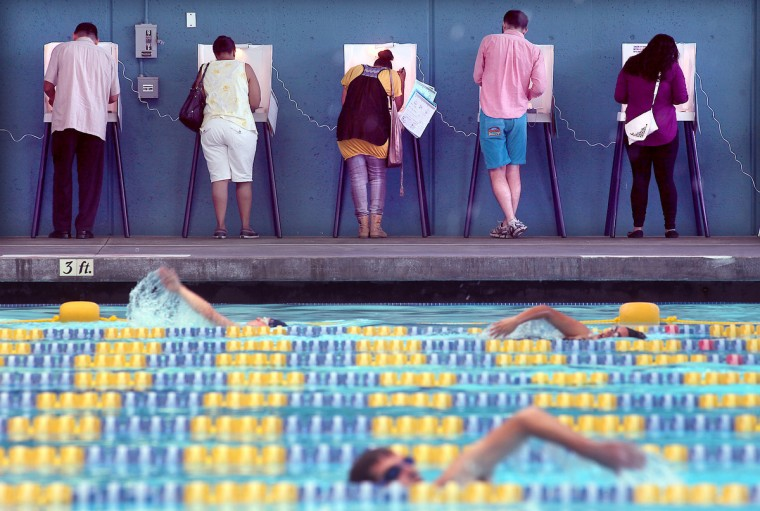 Voters cast their ballots as swimmers take laps at Echo Park Pool on Tuesday, November 6, 2012, in Los Angeles, California. (Brian van der Brug/Los Angeles Times)