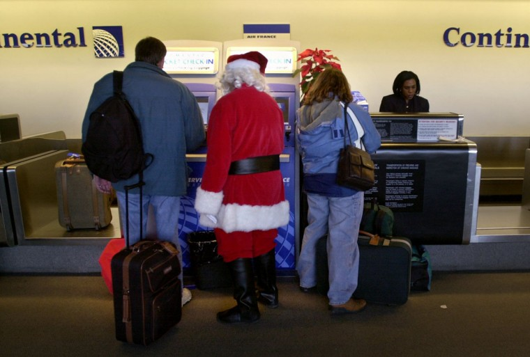 Santa Claus, aka Paul Herwit, a Continental Airlines employee, assists passengers with using the electronic ticket check-in on December 22, 2000 in Baltimore, Maryland. (Linda Coan/Baltimore Sun)