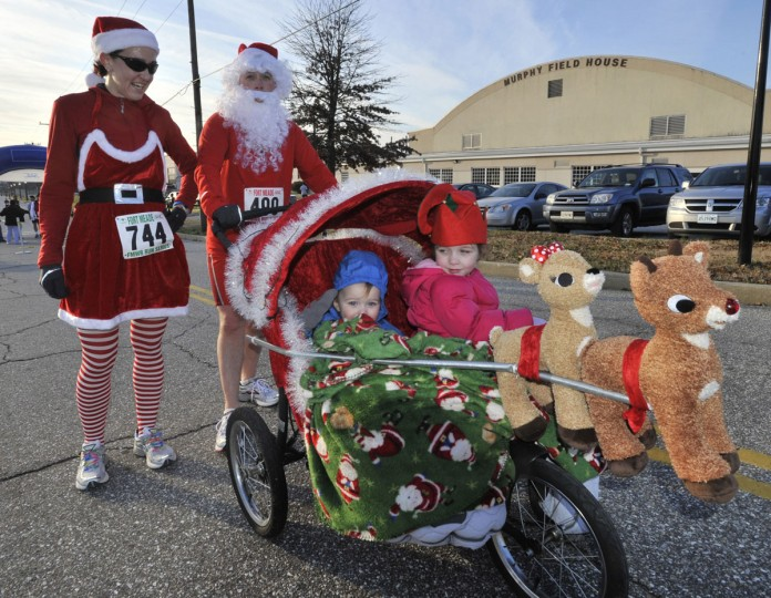Capt. Jeremy Fisher (Santa) and his wife, Sarah, were in the Christmas spirit as they finished the 5K Reindeer Run with their children, Jeremiah (left), 1, and Sophia, 5. (Phil Grout/Patuxent Publishing)