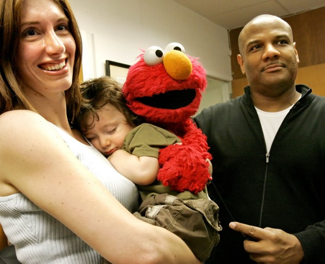 Oblivious to the excitement, 18-month-old Logan Haerian of Cockeysville sleeps on his mother's shoulder while a photograph of him is taken alongside Elmo and puppeteer Kevin Clash. (Justin Kase/Baltimore Sun Media Group)