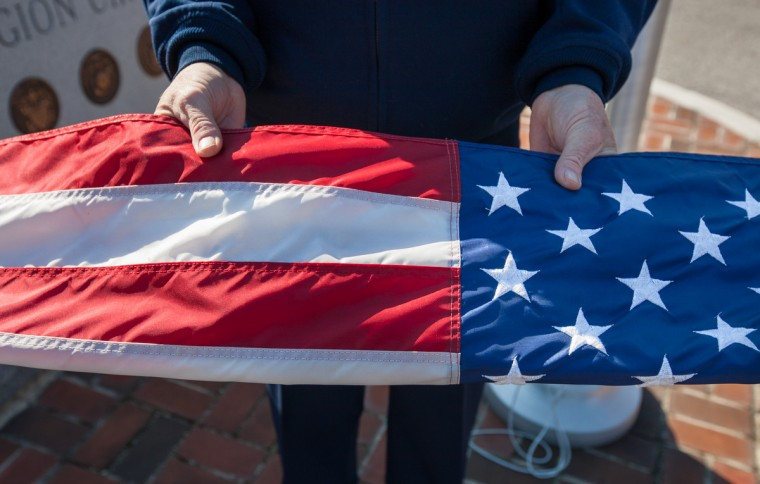 Legion Post 60 member Marvin Rogers, of Laurel, holds the center of a flag that is being folded and retired. (Nate Pesce/Baltimore Sun Media Group)