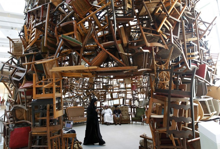"""A visitor walks within an installation titled """"Chairs"""", made of wooden chairs by Japanese artist Tadashi Kawamata, during Abu Dhabi Art at Saadiyat island, off the coast of Abu Dhabi. The annual art fair which showcases modern and contemporary art, opens on Wednesday and runs till November 10. (Jumana ElHeloueh/Reuters)"""