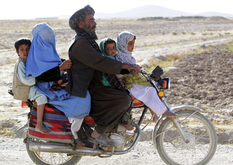Residents riding on a motorcycle look at U.S. Marines of Police Advisory Team Now Zad, 2nd Battalion, 7th Marines Regiment (not pictured) as they pass an Afghan police checkpoint at Now Zad district in Helmand province, southwestern Afghanistan November 8, 2012. (Erik De Castro/Reuters photo)