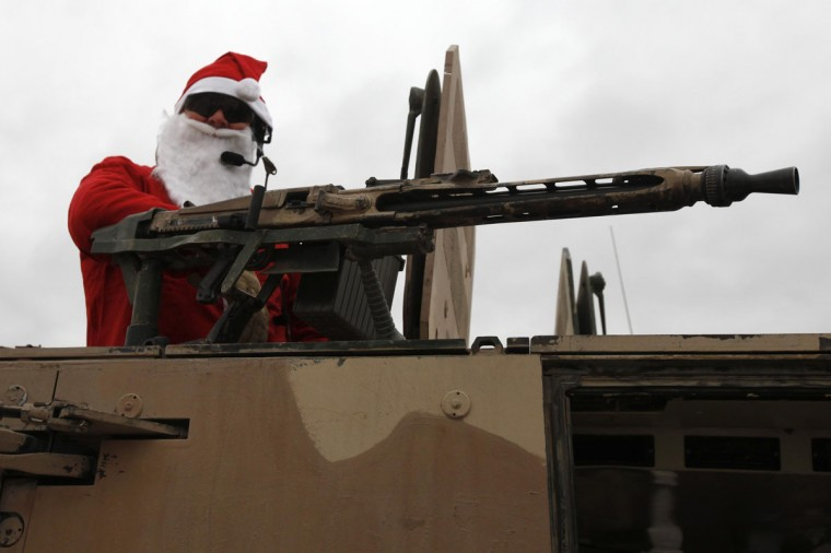 A German Bundeswehr army soldier with the Delta platoon of the 2nd paratroop company 373 wearing a Santa Claus costume stands atop an armoured vehicle before leaving the army camp for a mission in Kunduz, northern Afghanistan, December 6, 2010. (Fabrizio Bensch/Reuters)