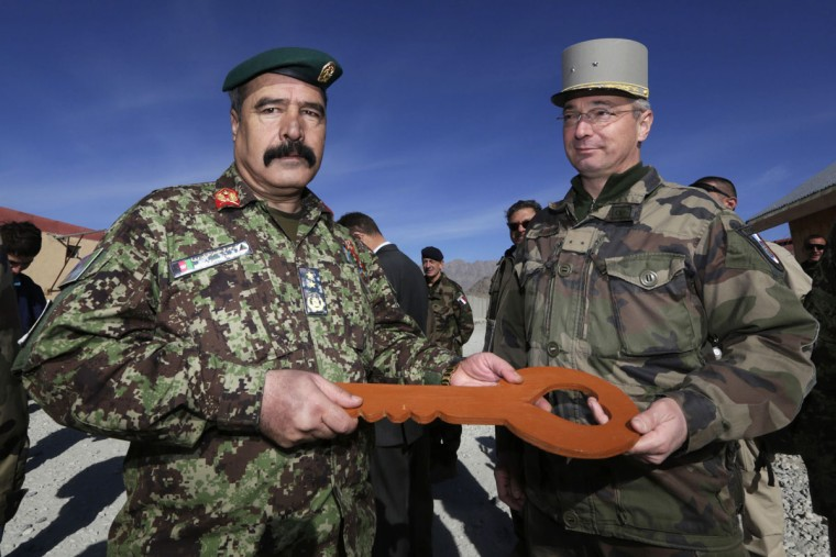 French General Eric Hautecloque Raysz (R) gives the symbolic key of the base to his Afghan counterpart General Mohammad Zaman Waziri during a handover ceremony between the French army and the ANA (Afghan National Army) at the forward operational base of Nijrab, as part of the withdrawal of French troops. French combat troops are due to pull out of Afghanistan by the end of the year. (Eric Gaillard/Reuters)