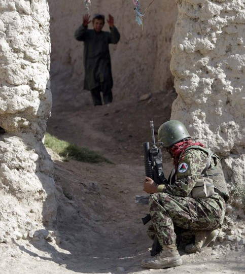 An Afghan soldier of 215th Maiwand Corps takes up position in an alley during a joint patrol with U.S. marines of Fox Co, 2nd Battalion, 7th Marines Regiment in a village at Musa Qal-Ah district in Helmand province, southwestern Afghanistan. (Erik De Castro/Reuters photo)