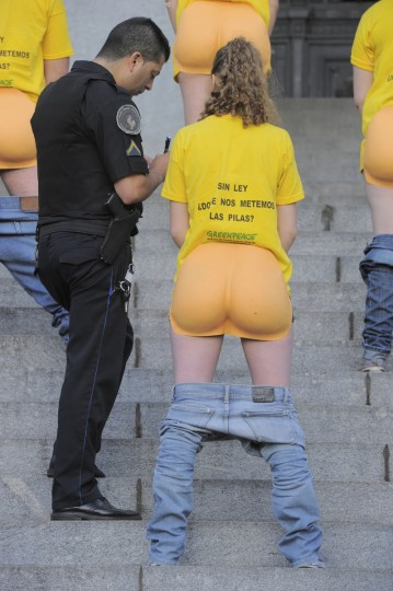 """A police officer questions an activist, wearing a prosthetic buttock, from environmental group Greenpeace during a demonstration at the stairs of the National Congress in Buenos Aires. The organization demands the Congress approve a new law on electronic waste. Her T-shirt reads, """"Without law on electronic waste, where do you want us to put the batteries?"""" (Greenpeace/Reuters)"""