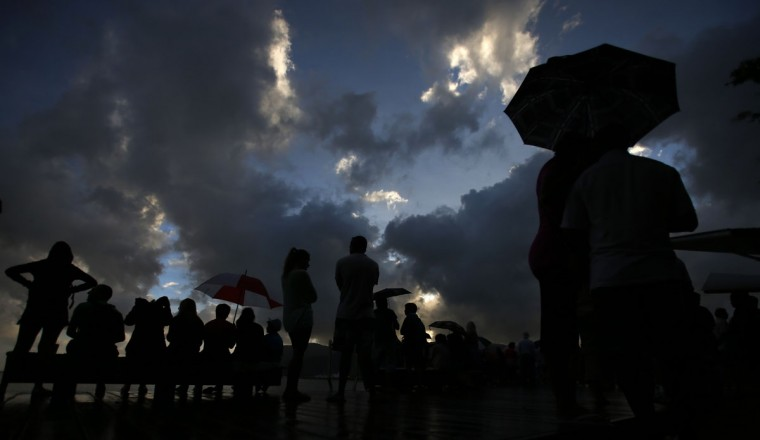 Rain showers fall as tourists look at a cloudy sky as a full solar eclipse begins in the northern Australian city of Cairns November 14, 2012. (Tim Wimborne/Reuters)