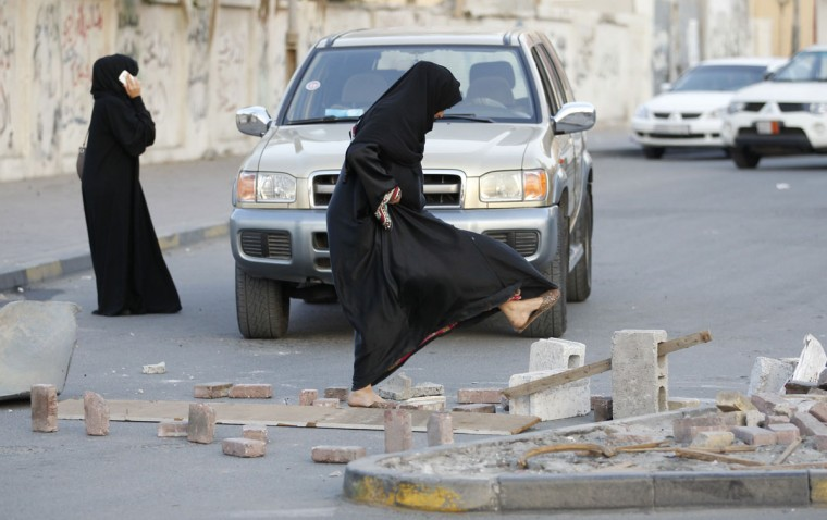 A woman kicks way a wooden block to open the road which was blocked by anti-government protesters during clashes in the village of Sanabis west of Manama, Bahrain. Hundreds of protesters march on the street of the village defying the ban on protests set by Bahrain's Ministy of Interior. (Hamad I Mohammed/Reuters)