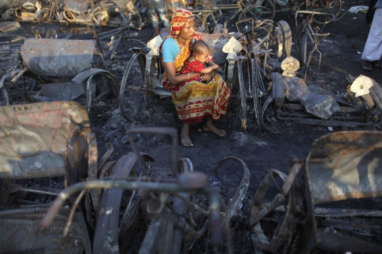Taslima Akhter sits with her six-month-old daughter Fatema among the burnt remains of homes in a slum after a fire at Hazaribagh area in Dhaka. Thousands of people were still living under the open sky after a deadly fire, which killed at least 14 people and burnt 500 thatched houses at a slum in Dhaka on Sunday, local media reported. (Andrew Biraj/Reuters)