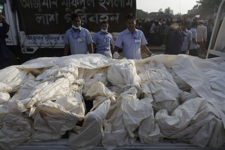 Bodies of unidentified garment workers, who died in a devastating fire in a garment factory, lie in a truck before a mass burial at a graveyard in Dhaka. Bangladesh said on Tuesday a fire that killed 111 textile workers was sabotage as protesters took to the streets for a second day and garment factories across the world's second biggest clothes exporter stopped work to mourn. (Andrew Biraj/Reuters)