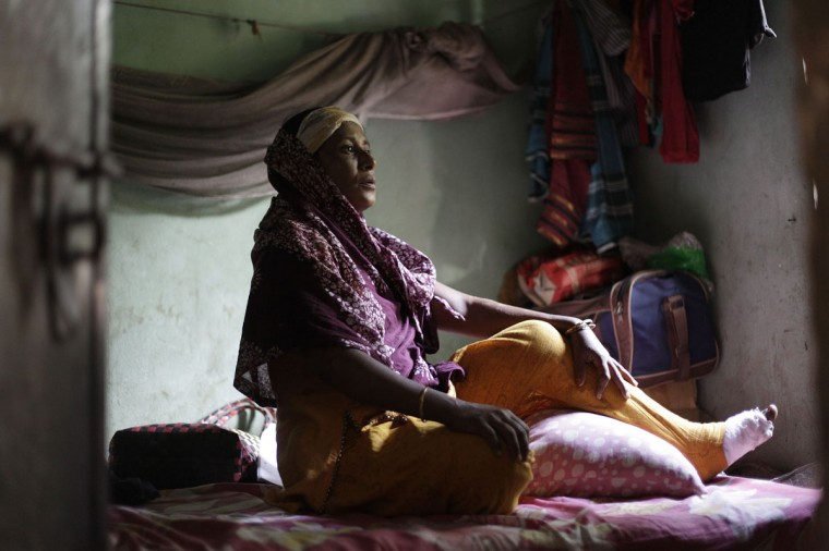 Ale Noor, 35, who survived a devastating fire at a garment factory, sits inside her slum room in Savar. Noor, an operator of Tazreen Fashions garment factory, escaped the fire which killed more than 100 workers on November 24. According to Noor, she broke her left leg after jumping from the fourth floor to escape the fire. Noor earns 3,000 Taka ($37) per month, but she says the factory's workers have had to protest to receive their pay each month as the factory's management never paid their salaries on time. (Andrew Biraj/Reuters)