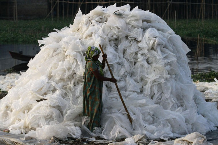 A woman dries used polythene sheets after washing them on the bank of the river Buriganga in Dhaka November 11, 2012. According to the workers, the polythene sheets will be sold to a recycling plant. (Andrew Biraj/Reuters)