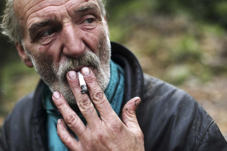 Former steel factory worker Zarko Hrgic, 57, smokes in front of his cave near Babina river in Babino village, near the central Bosnian town of Zenica. Hrgic has been living there since he was deported five years ago for staying illegally in Germany. His day starts with searching for food discarded in garbage bins in cities, as well as cigar butts, from which he makes improvised cigars. Picture taken November 3, 2012. (Dado Ruvic/Reuters)
