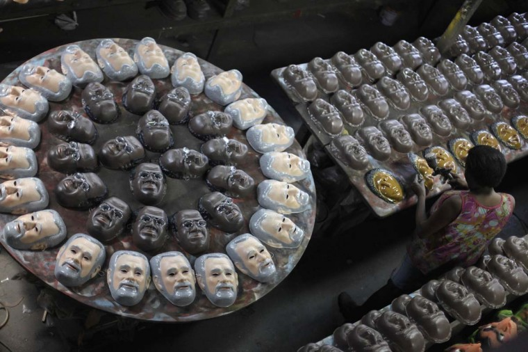Carnival masks bearing the likeness of Brazil's Supreme Court Justice Joaquim Barbosa (center of circle) and Jose Genuino, former president of the Workers' Party of former President Luiz Inacio Lula da Silva, are pictured on a factory assembly line in Sao Goncalo, near Rio de Janeiro. (Ricardo Moraes/Reuters photo)