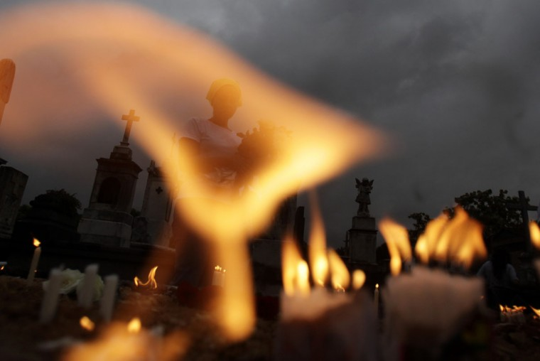 A woman prays after lighting candles in memory of her loved ones as she commemorates the Day of the Dead in Rio de Janeiro November 2, 2012. (Ricardo Moraes/Reuters)