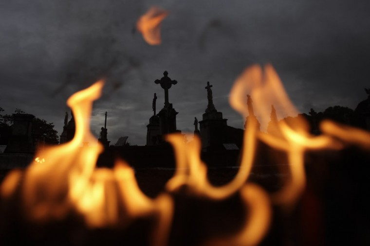 Tombs are pictured behind the fire of candles lighted by the faithful in memory of their loved ones as they commemorate the Day of the Dead in Rio de Janeiro November 2, 2012. (Ricardo Moraes/Reuters)