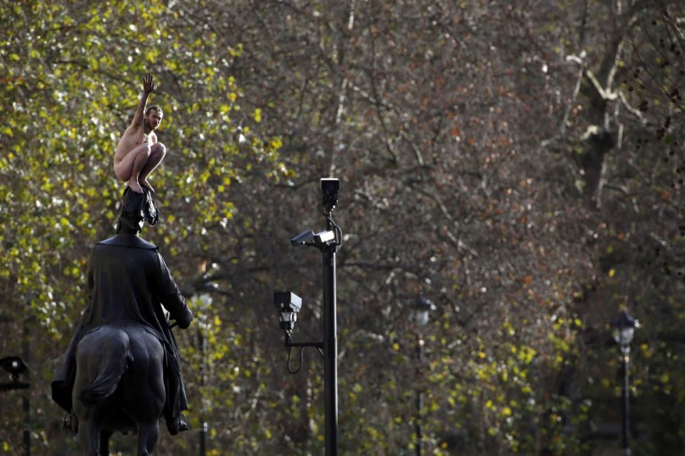 A naked man gestures on a statue in Whitehall, central London. The man posed on a statue of Prince George, the Duke of Cambridge, in front of onlookers for nearly three hours on Friday before he was coaxed down and put into the back of a police van shortly after 3pm. (Stefan Wermuth/Reuters)