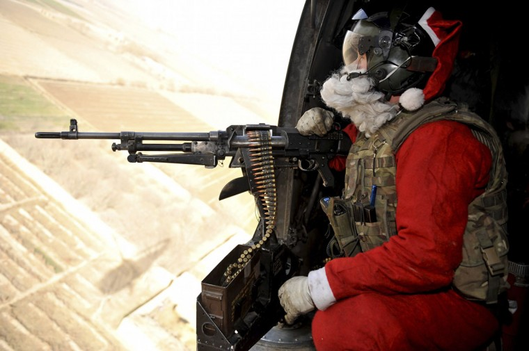 Door Gunner Petty Officer Richard Symonds of the Royal Navy wears a Santa Claus outfit as he delivers mail and presents to troops around Helmand province in this handout released by Britain's Ministry of Defence December 25, 2010. (Sgt Rupert Frere RLC/Crown Copyright/Handout/Reuters)