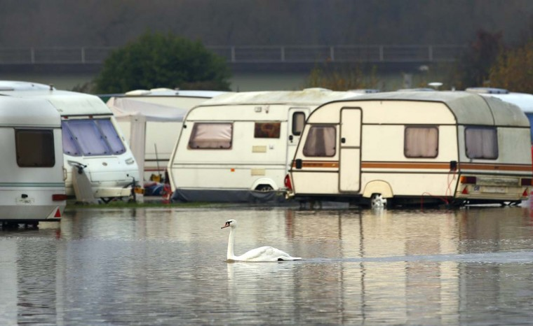 A swan swims through flood waters from the River Soar at a caravan park in Barrow Upon Soar, central England, November 26, 2012. (Darren Staples/Reuters)