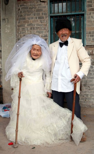 Wu Conghan, 101 years old, and his 103-year-old wife pose for photos while wearing wedding clothes at their home in a village of Nanchong, Sichuan province. The couple had their first photo taken in wedding suit and dress after being married for 88 years. (Rueters/China Daily)