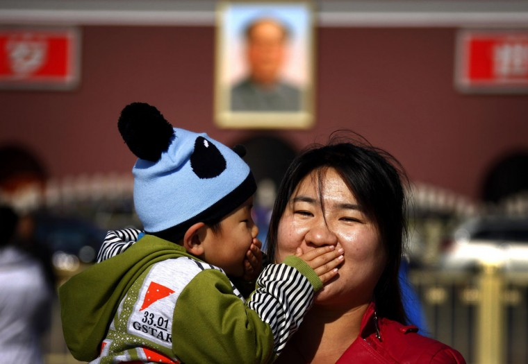 A young boy covers the mouth of his mother as they pose for a photograph in front of the giant portrait of former Chinese Chairman Mao Zedong on Beijing's Tiananmen Square November 12, 2012. Security has been tightened around the square and the adjoining Great Hall of the People where the 18th National Party Congress (NPC) is currently taking place. (David Gray/Reuters)