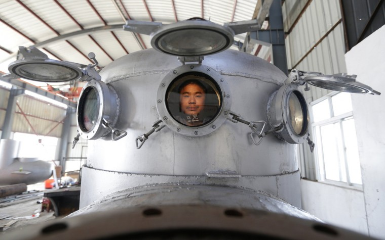 Zhang Wuyi sits in his newly made multi-seater submarine at his new workshop near an artificial pool in Wuhan, Hubei province. Zhang, a 37-year-old local farmer, who is interested in scientific inventions, has independently made seven miniature submarines with several fellow engineers, one of which was sold to a businessman in Dalian at a price of 100,000 yuan ($15,855) last October. The submarines, mainly designed for harvesting aquatic products, such as sea cucumber, have a diving depth of 20-30 metres (66-98 feet), and can travel for 10 hours, local media reported. (Reuters)