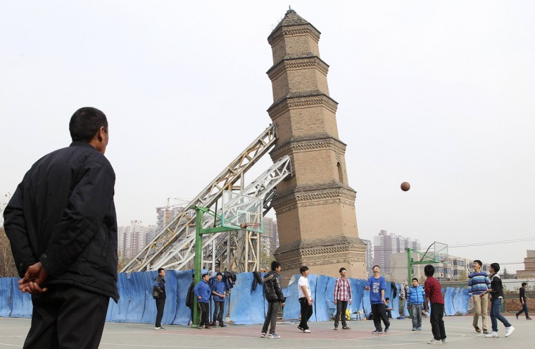 Students play basketball beside a leaning tower at school playground in Xi'an,Shaanxi province. The Wanshousi tower, located at a middle school playground, was built during Ming Dynasty (1368-1644). It has been tilting since the 1960s, and is now supported by steel frames, local media reported. (Reuters)