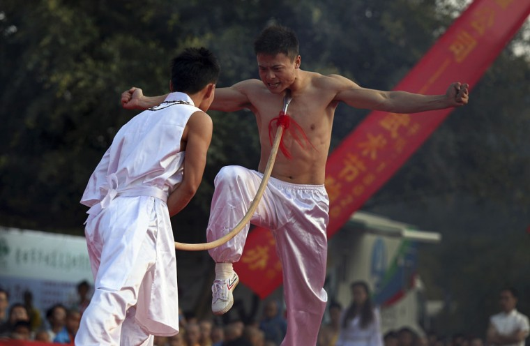 Practitioners perform qigong, a type of traditional Chinese martial arts, during the opening ceremony of the fourth Southern Shaolin Martial Arts Cultural Festival in Putian city, Fujian province, November 1, 2012. (China Daily/Reuters)