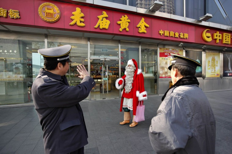 A man dressed as Santa Claus walks past two security guards in downtown Shanghai December 23, 2010. Officially recognized by the Finland government after a four-year training, the man is one of 50 officially registered Santa Clauses who is paying a visit to Shanghai, warming up the Christmas holidays. (Aly Song/Reuters)