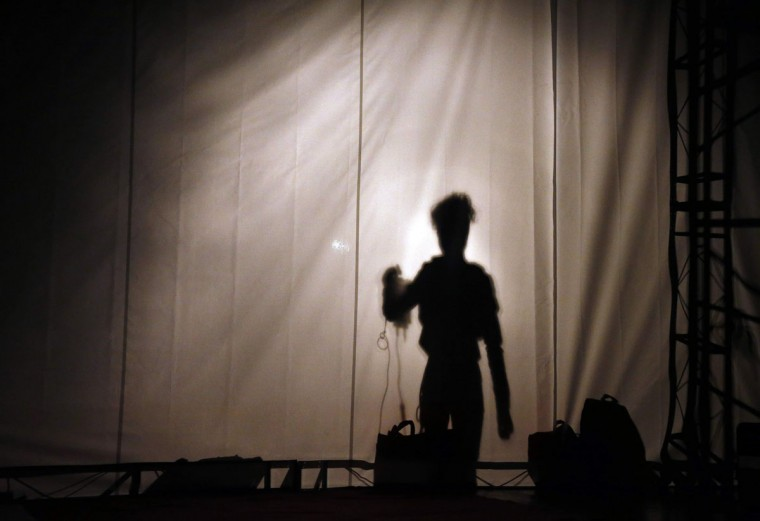 A model's shadow is cast onto a curtain before the start of a fashion show organised by environmental group Greenpeace titled 'Toxic Threads - The Big Fashion Stitch-Up' in Beijing. According to a recent Greenpeace study, major global fashion labels are using toxic chemicals in the production of their clothing, which occurs mainly in China, that leads to environmental degradation. (David Gray/Reuters)