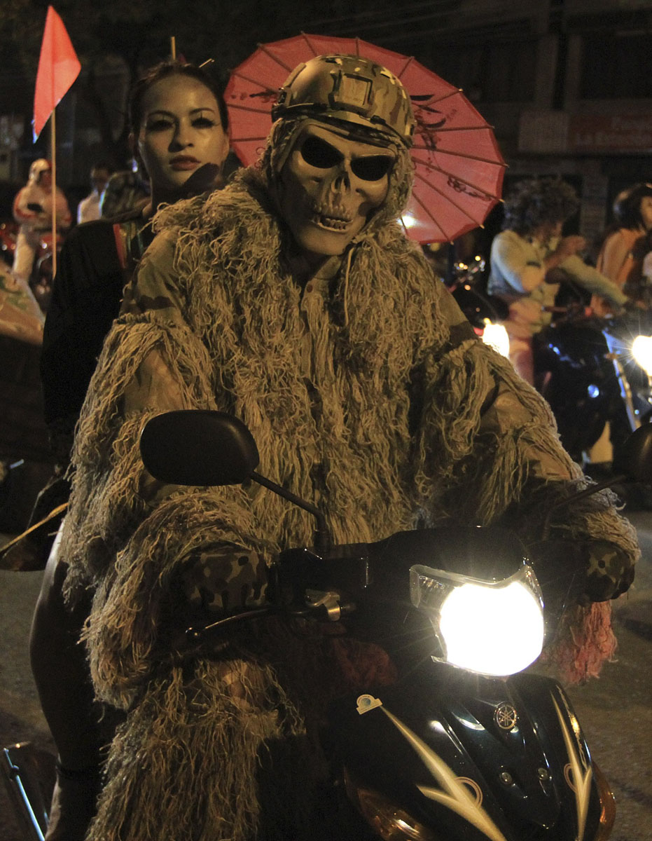 A couple dressed in costumes rides a motorbike during the 'Moto ...