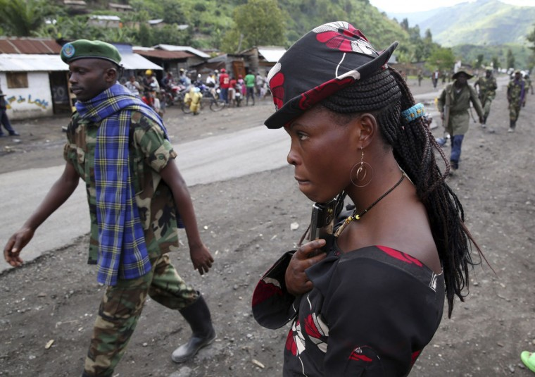 A M23 rebel fighter walks past a resident as they withdraw from the town of Sake, some 27 km (17 miles) west of Goma, Democratic Republic of Congo.. (Goran Tomasevic/Reuters)