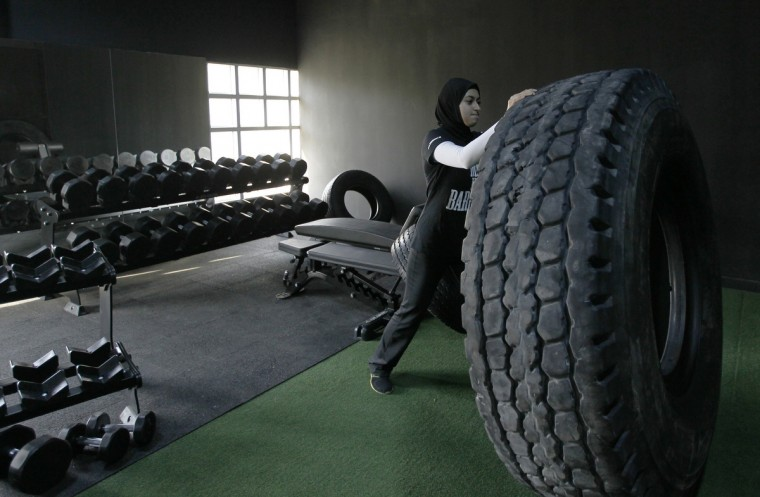 Emirati weightlifter Amna Al Haddad pushes a tyre during a training session at Fast Performance Center in Ahdaaf Sports Club in Dubai. Al Haddad, 23, a former CrossFit enthusiast and currently an Olympic weightlifter, hopes to make it to the 2016 Olympics in Rio de Janeiro. (Jumana El Heloueh/Reuters)
